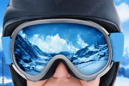 A mountain range reflected in the ski mask. Girl wearing a ski mask