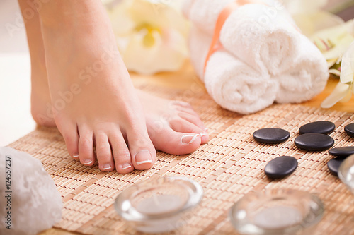 Poster Pedicure Closeup photo of a female feet with white french pedicure on nails. at spa salon. Legs care concept