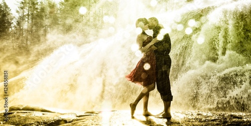 Girl in red dress kissing man by waterfall in morning light