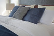 Gray and deep blue pillows on bed and white reading lamp in background