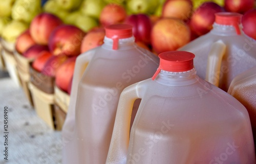 apple cider in jugs with apples at the farmers market Wallpaper Mural