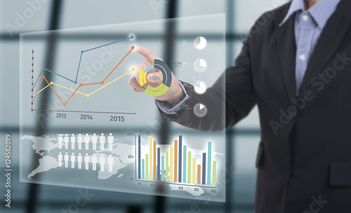 Fotografía  Businessman touching financial analysis graph with key performance indicators on virtual screen