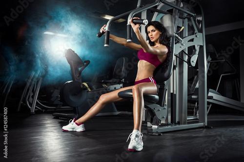 Fototapeta Fitness, trening, młoda piękna dziewczyna trenuje na siłowni obraz