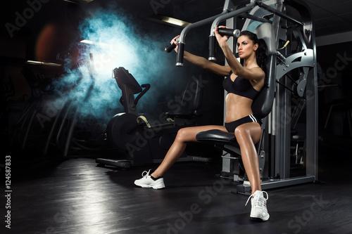 Fototapeta premium Fitness, trening, młoda piękna dziewczyna trenuje na siłowni