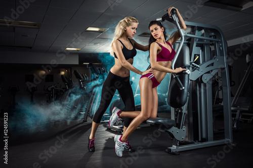 Fototapeta premium Fitness, trening, trener osobisty, dwie dziewczyny trenują na siłowni