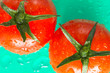 Two red tomatoes with green leaves. Top view. Green background.