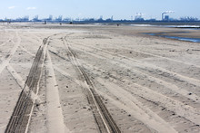 Tire Tracks On The Beach And Rotterdam Industry In Background