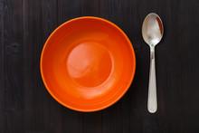Orange Bowl And Spoon On Dark Brown Table