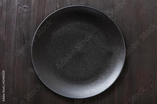 top view of black plate on dark brown table