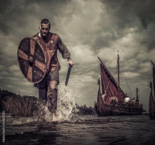 Foto  Wikinger-Krieger im Angriff, entlang der Küste mit Drakkar auf Hintergrund ausge