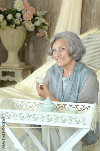Foto op Canvas Kruidenierswinkel Elderly woman on bed with tea