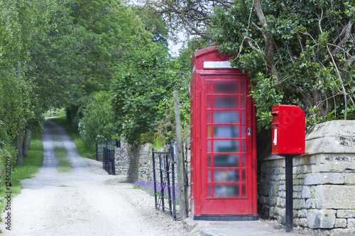 Papiers peints Rouge, noir, blanc Traditional English red telephone and post box by a dirty road in a rural village