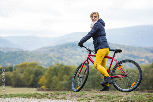 Fototapeta Urban biking - woman riding bike in city park  obraz na płótnie