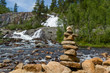 Traditional norwegian stone pyramid on the waterfall background.