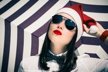 Portrait Of A Pretty Girl In Santa Claus Hat And  Sunglasses