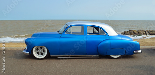 Customized blue vintage car on seafront promenade, sea and beach in background. .