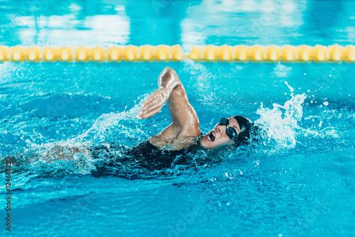 Zdjęcie XXL Pływak na treningu. Żeński dopłynięcie frontowy czołg w salowym basenie
