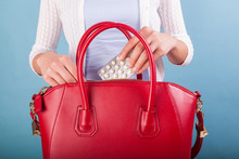 Woman Putting Pills To Red Bag