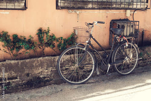 vintage bicycle parked at old wall in the urban narrow street (vintage color tone styles) © jakkapan
