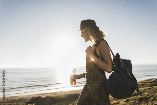 Blond teenage girl with backpack and beverage at seaside in the evening twilight
