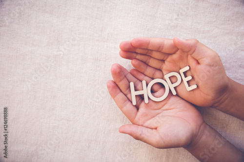 Fototapeta HOPE wooden word on praying hands , gratitude, faith concept