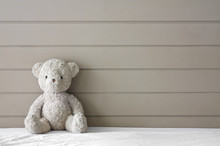 Teddy Bear Sit On The Left Side White Bed At Headboard And Brown