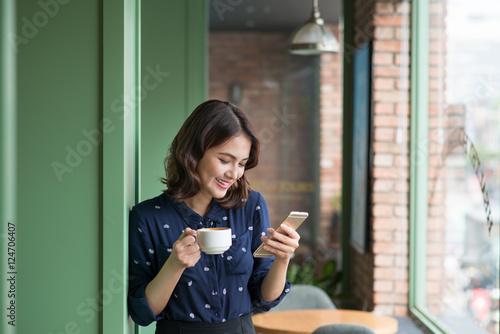 Fotografie, Obraz  Beautiful cute asian young businesswoman in the cafe, using mobi