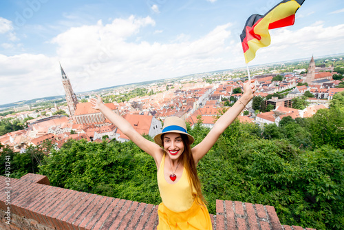 Photo Stands Nice Young female tourist with german flag on the bavarian town background in Landshut