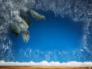 Fototapeta Boże Narodzenie/Nowy Rok Frozen window and Christmas tree in snow against it.