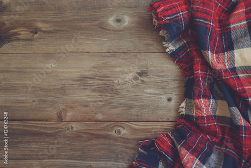 Fototapeta Flat lay view of tartan textured scarf on wooden background with obraz