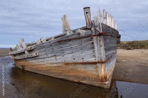 Keuken foto achterwand Schip Old wooden ship stranded on a sandy beach. Laptev sea. Yakutia. Russia.