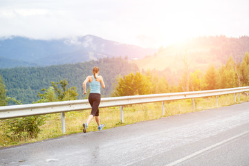 Young athletic woman jogging on road in mountains