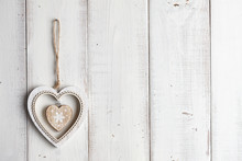 Valentine Heart Hanging Over White Wooden Fence. Christmas Decoration.