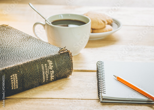 Photo image of the old book with small note book, pencil and a cup of coffee on wooden
