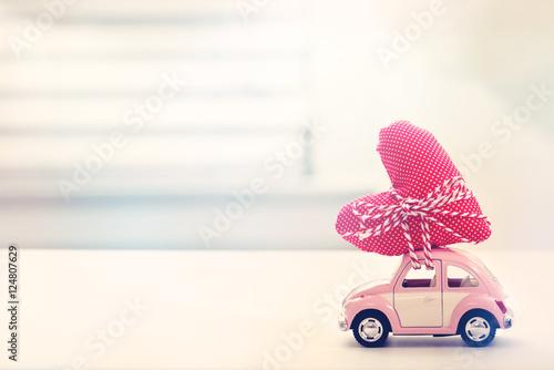 Keuken foto achterwand Vintage cars Miniature pink car carrying heart cushion