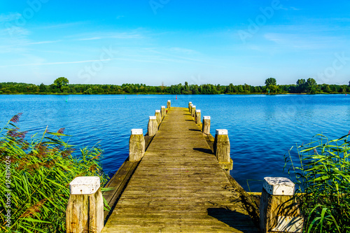 Fotografía A mooring dock for boats in the bird sanctuary of Veluwemeer with reed along the