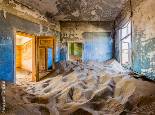 Fotografie, Obraz  Room full of sand with colored door in the ghost town of Kolmanskop, Namibia