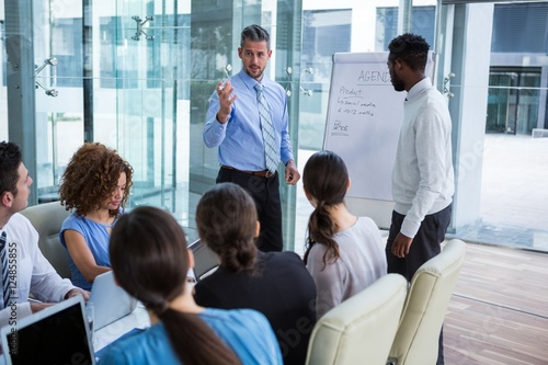 Valokuva  Businessman discussing on white board with coworkers