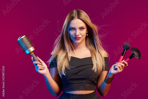 Female stylist standing with hairdresser's accessories and makeup brushes