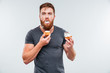 Filthy bearded young man eating cream cakes