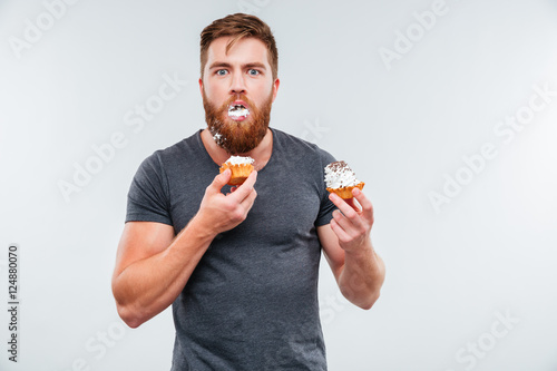 Photo  Filthy bearded young man eating cream cakes