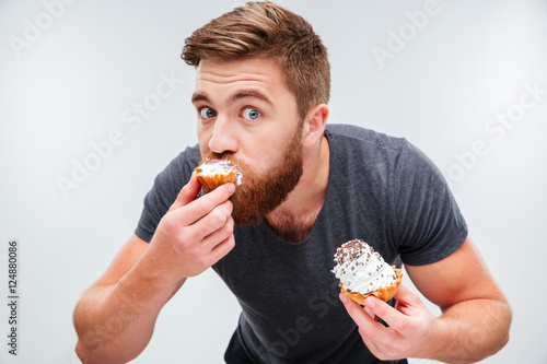 Close up portrait of a hungry man biting cream cake Canvas Print