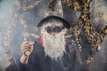 Wizard Merlin Conjures And Casts A Spell, Raising His Wand, A Old Man Dressed In A Stimpack Halloween Hipster Style