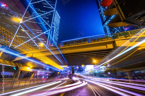 Plakat Futurystyczny nocny pejzaż widok z oświetlone drapacze chmur i ruchu miejskim po drugiej stronie ulicy. Hongkong