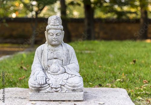 A small stone buddha at a green garden in Korea Canvas Print