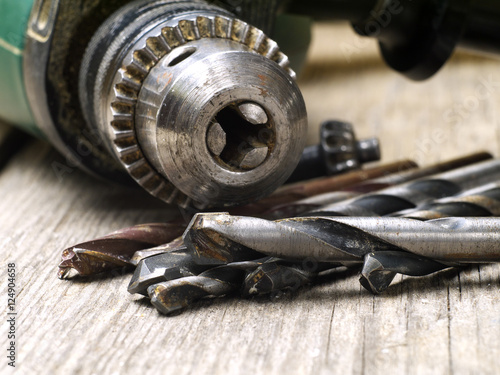 used drill machine chuck and twisted drill bit set closeup, shallow depth of fie Poster