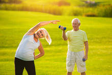 Senior Couple Does Exercises. Old People Outdoor. Strengthen Body And Improve Health. Fitness Is Available To Everyone.
