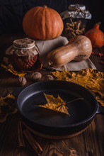 The Composition Of Pumpkin, Dried Rose Hips And Mushrooms With A Cast Iron Frying Pan On An Old Wooden Table