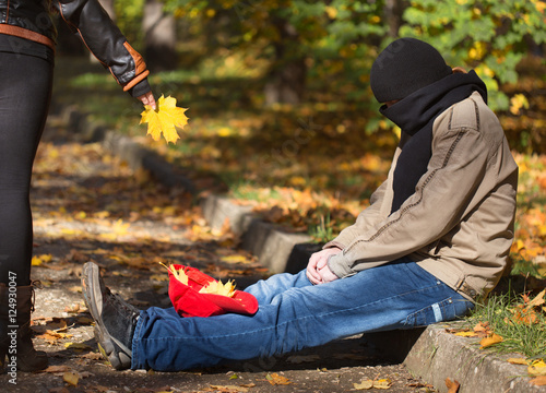 Valokuva  Metaphoric social photo with tramp man begging in autumnal park