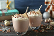 Delicious milkshakes with Christmas decoration on wooden table closeup